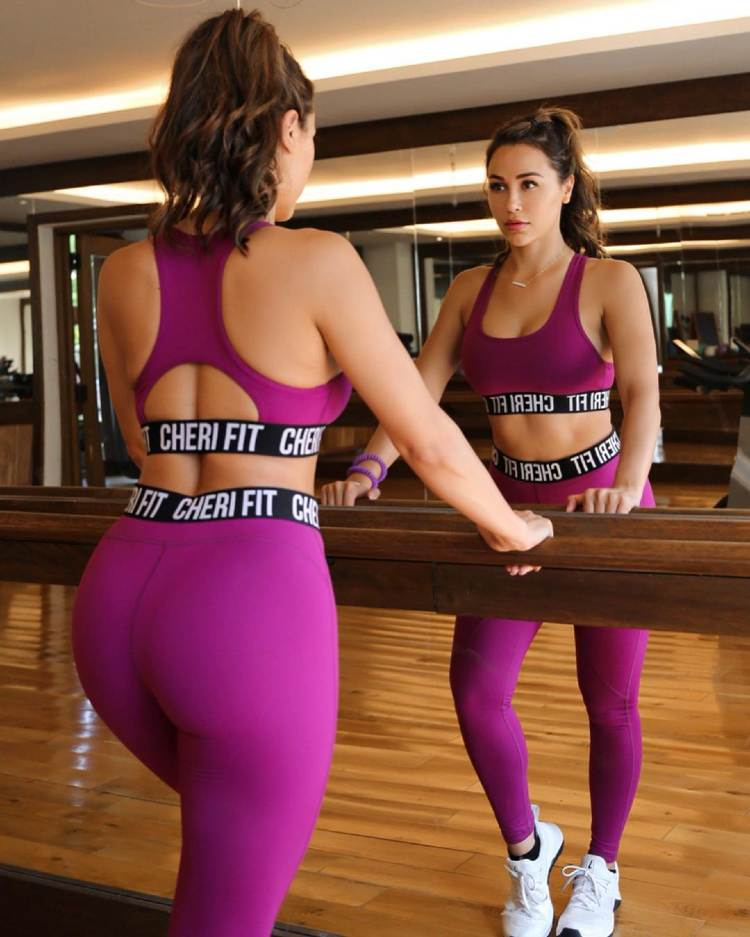 Ana Cheri in workout clothes, looking at herself in the mirror