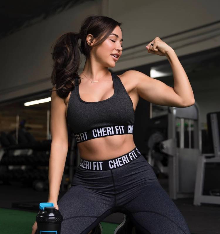 Ana Cheri flexing her biceps while smiling in the gym