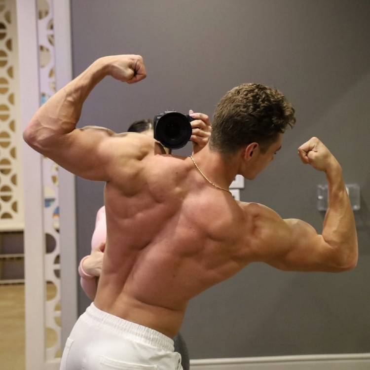 Colton Wergin showing off his muscular back in a back double biceps pose