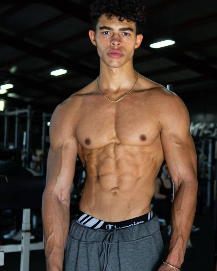 Devin Truss flexing shirtless in the gym