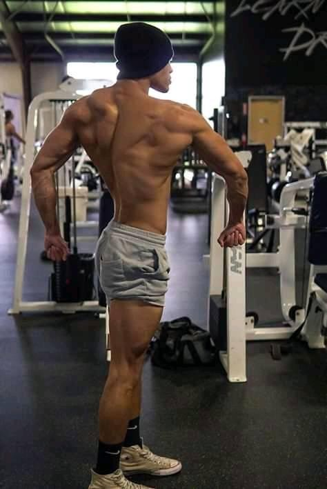 Devin Truss flexing his back muscles in a gym
