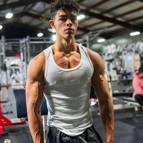 Devin Truss in a white tank top looking swole and ripped
