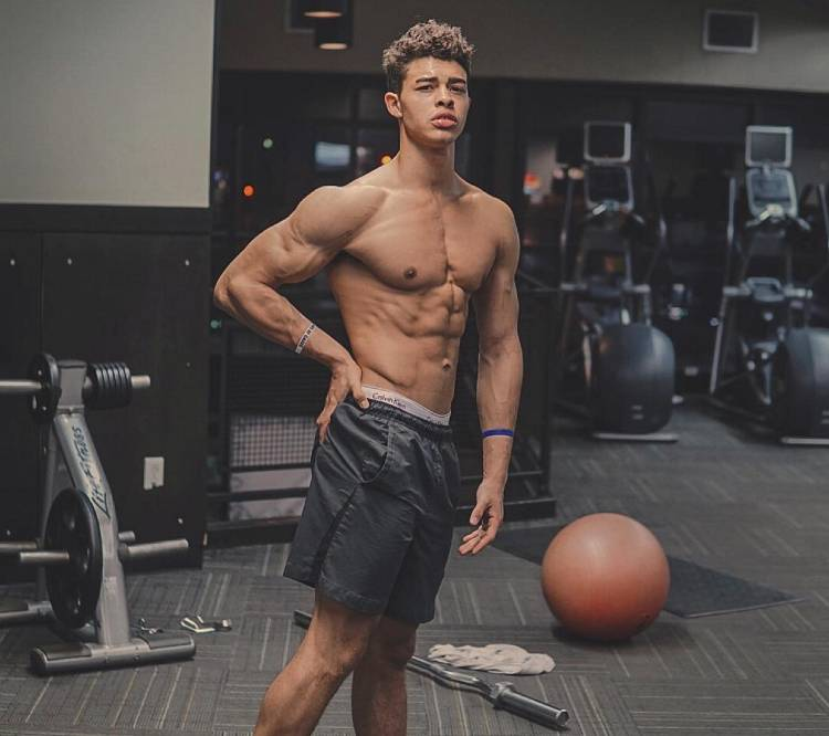 Devin Truss flexing his biceps and abs in a gym