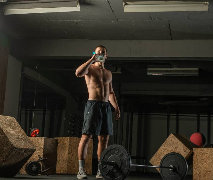 Shirtless and ripped man drinking a shake representing the best pre workouts for men
