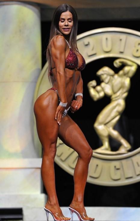 Sophie Gudiolin posing sideways on a fitness stage