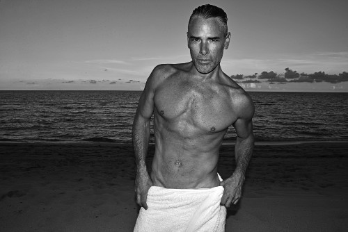 A black and white photo of a middle aged shirtless man showing off his lean body on the beach.