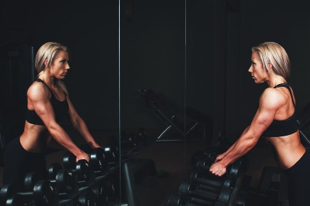 woman doing power training with dumbbells in the gym