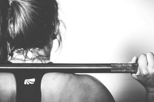 Picture of a woman's back with a barbell on top of it.
