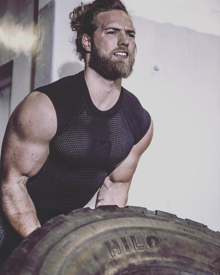 Ripped and muscular Lasse Matberg lifting a heavy tire.