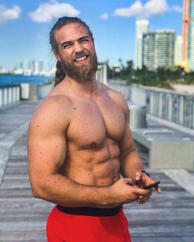 Shirtless Lasse Matberg standing on a pier and showing off his lean physique.