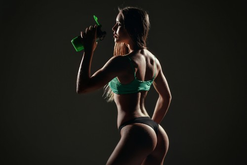 Lean and fit woman drinking the best pre workout supplement