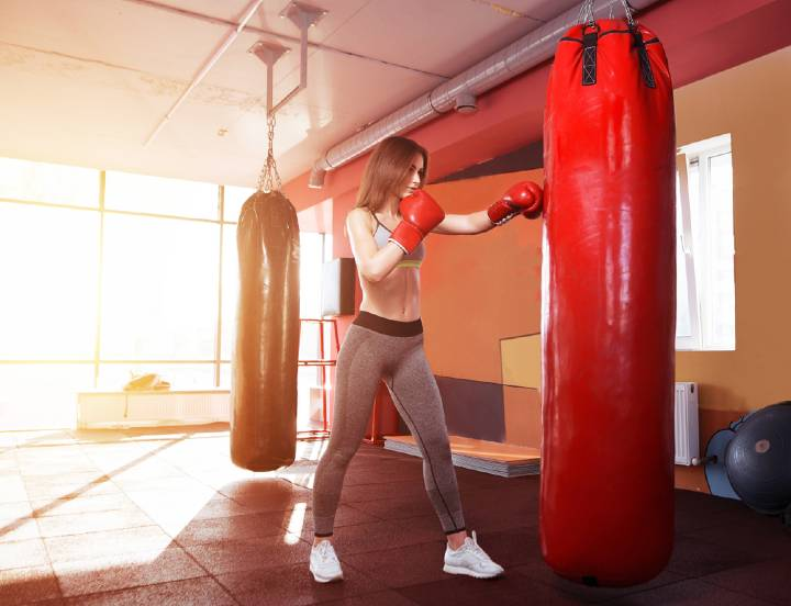 Young Woman practicing on boxing bag after taking a pre workout