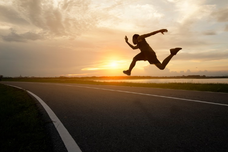 Runner jumping high on the road during a sunset after using best pre-workout for euphoria