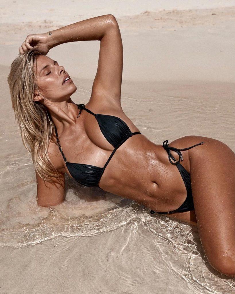 Natasha Oakley posing on a beach in a black bikini, looking ripped
