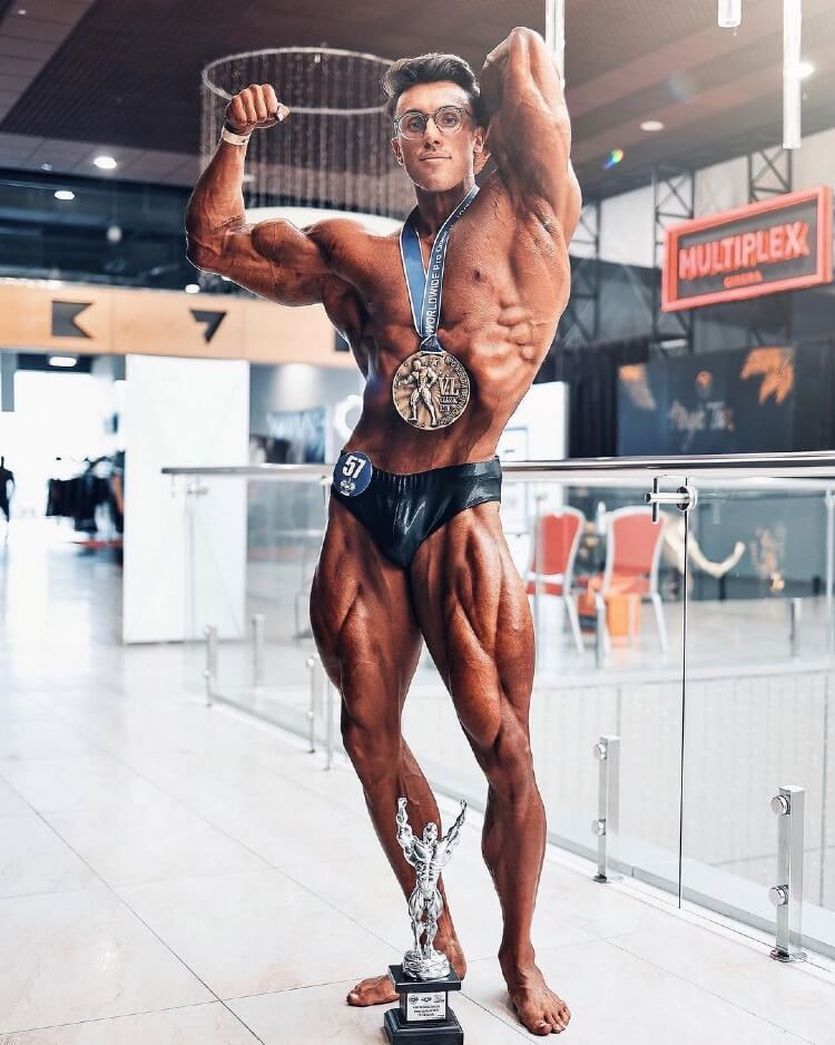 Brandon Harding flexing and showing off his ripped muscles, standing alongside a medal he won after a bodybuilding competition.