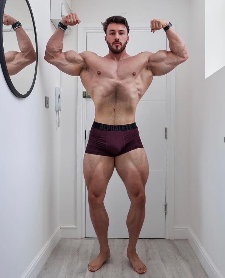 Brandon Harding posing shirtless in a house.