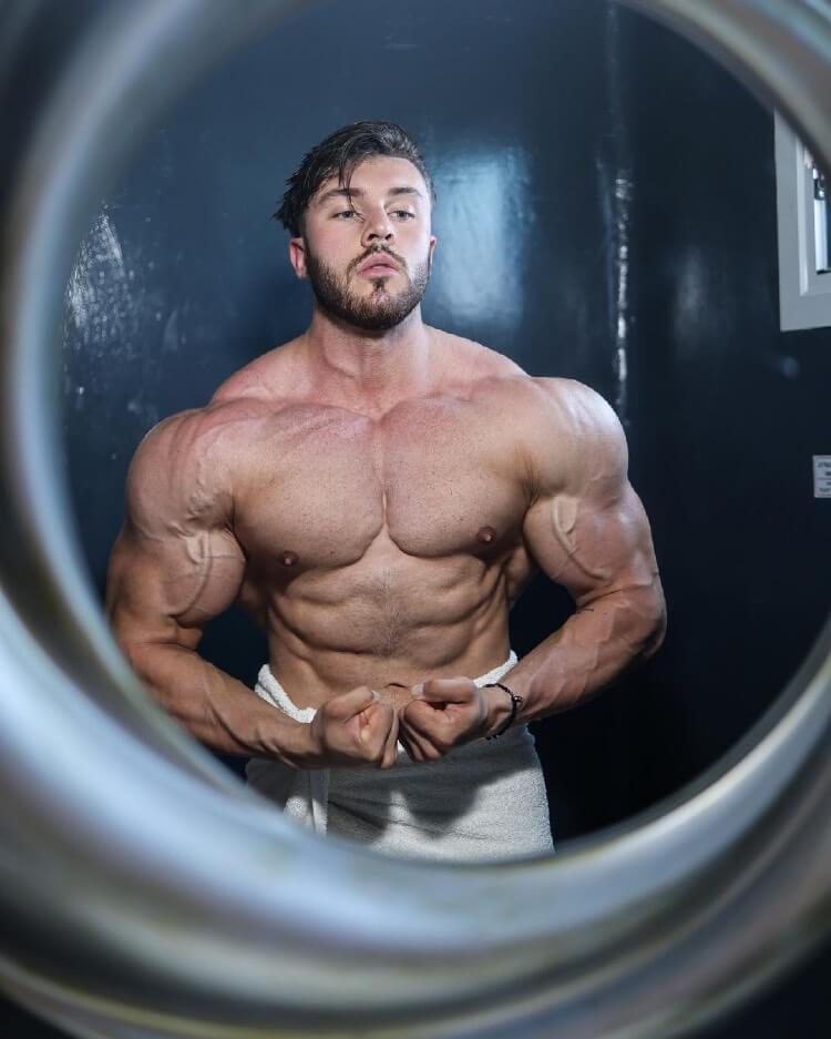 Brandon Harding flexing shirtless in front of a mirror.