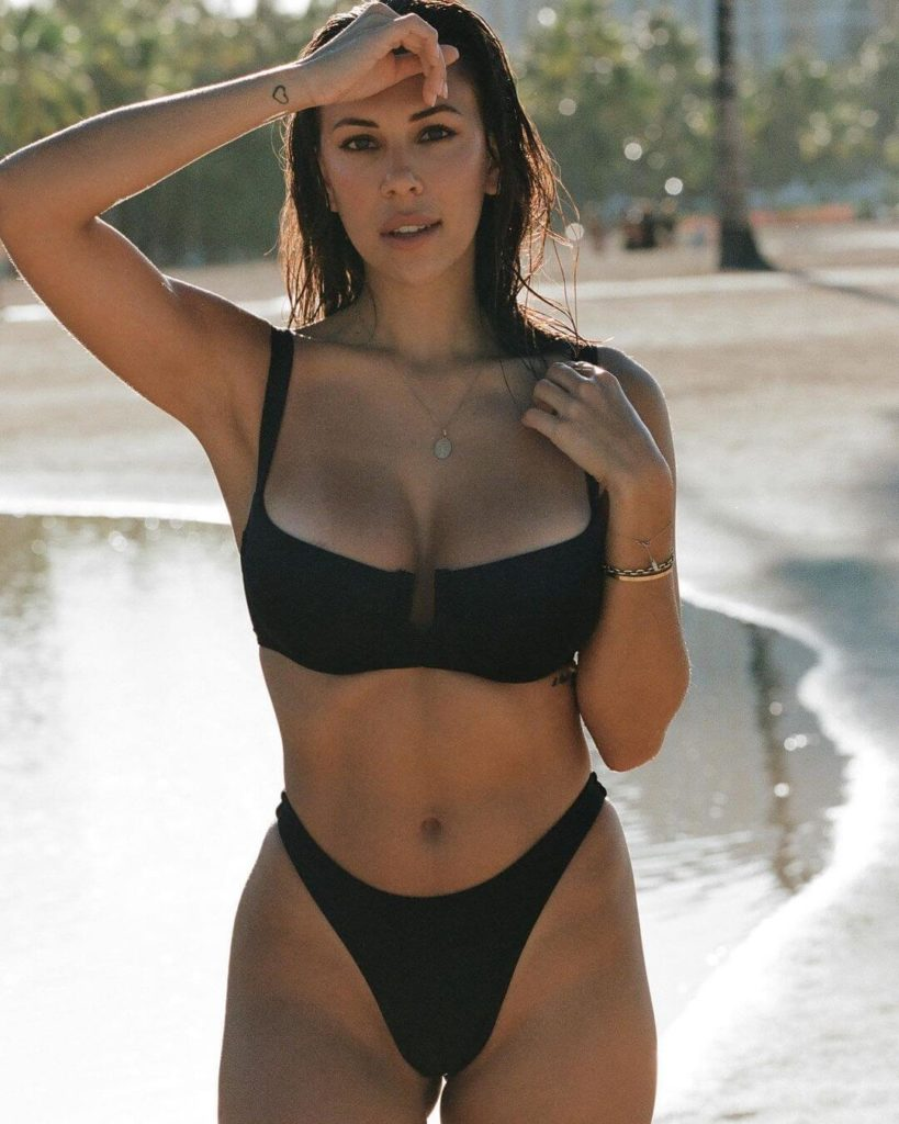 Devin Brugman looking fit and lean in her black bikini next to the sandy beach.