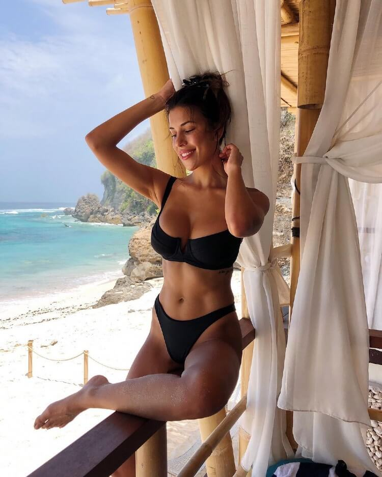 Devin Brugman sitting next to the beach in a bikini, looking lean and fit