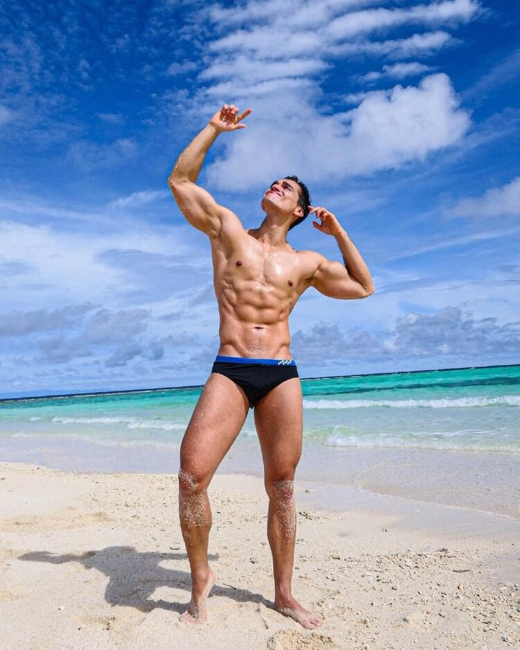 Hans Weiser hitting a Zyzz pose while shirtless on the beach