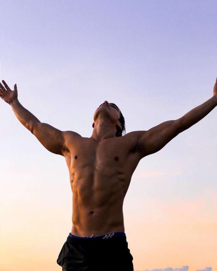 Hans Weiser standing shirtless with his hands spread out wide towards the sky.