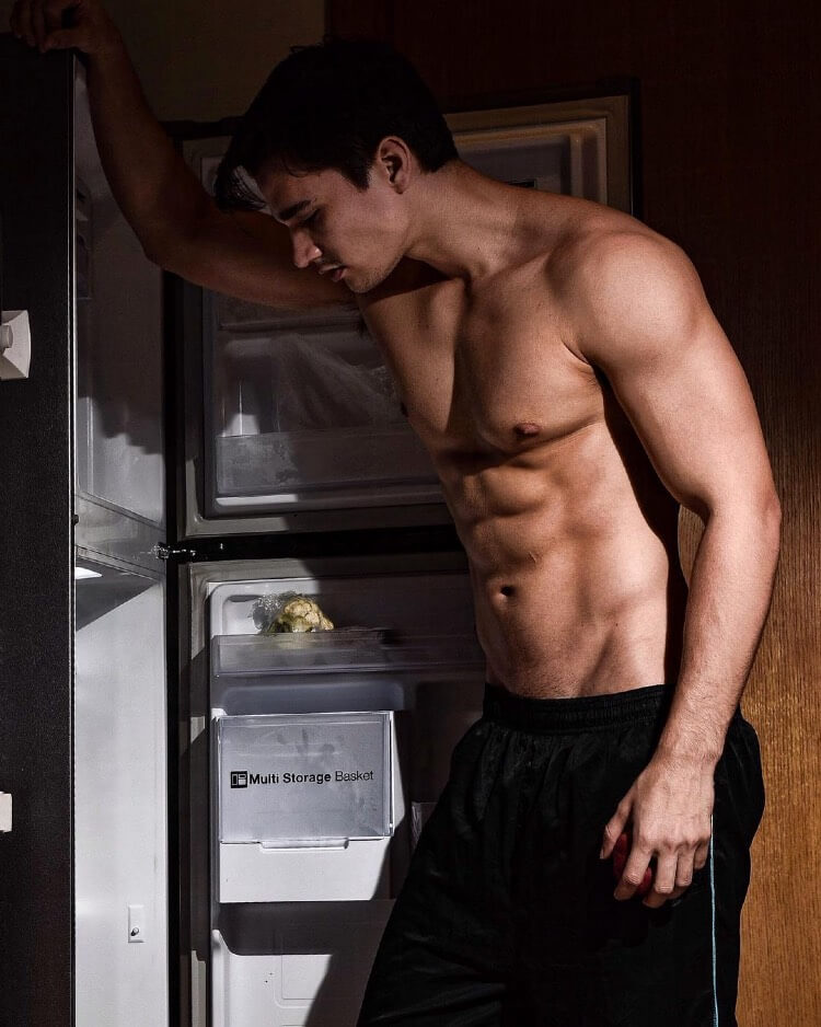 Hans Weiser posing shirtless in front of a fridge, looking lean and muscular.