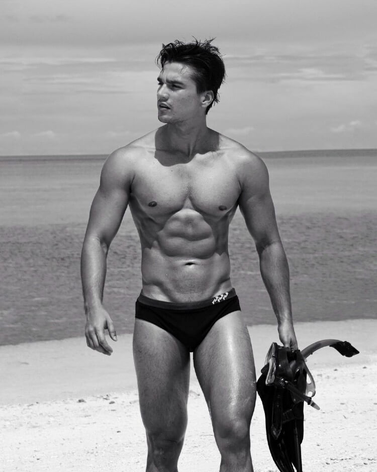 Hans Weiser walking shirtless down the beach in a black and white photo, looking ripped and chiseled.